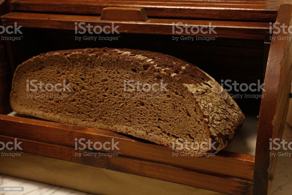 Half of black rye artisan bread loaf stock photo