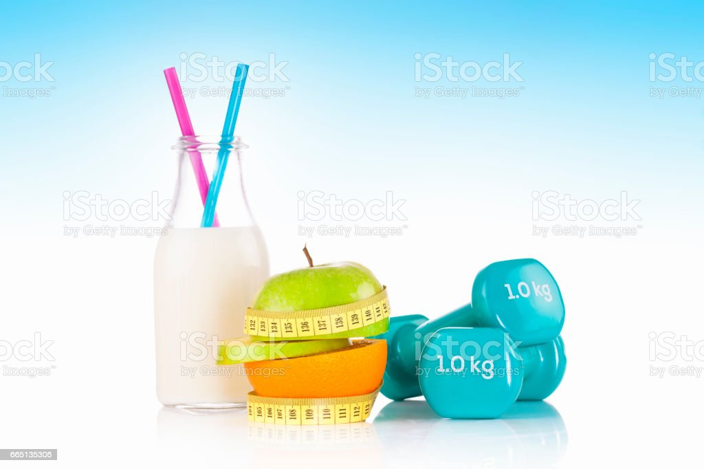 Half of green apple and orange wrapped with a plastic yellow tape measure. Healthy, organic food and diet concept stock photo