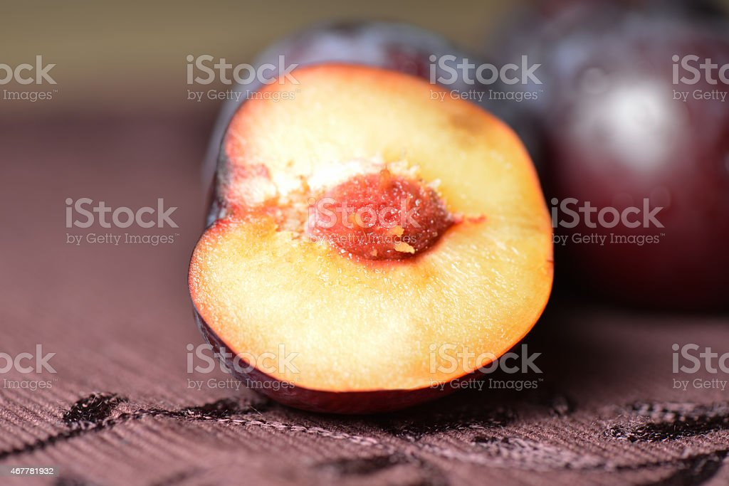 Half of plum on table cloth close up stock photo