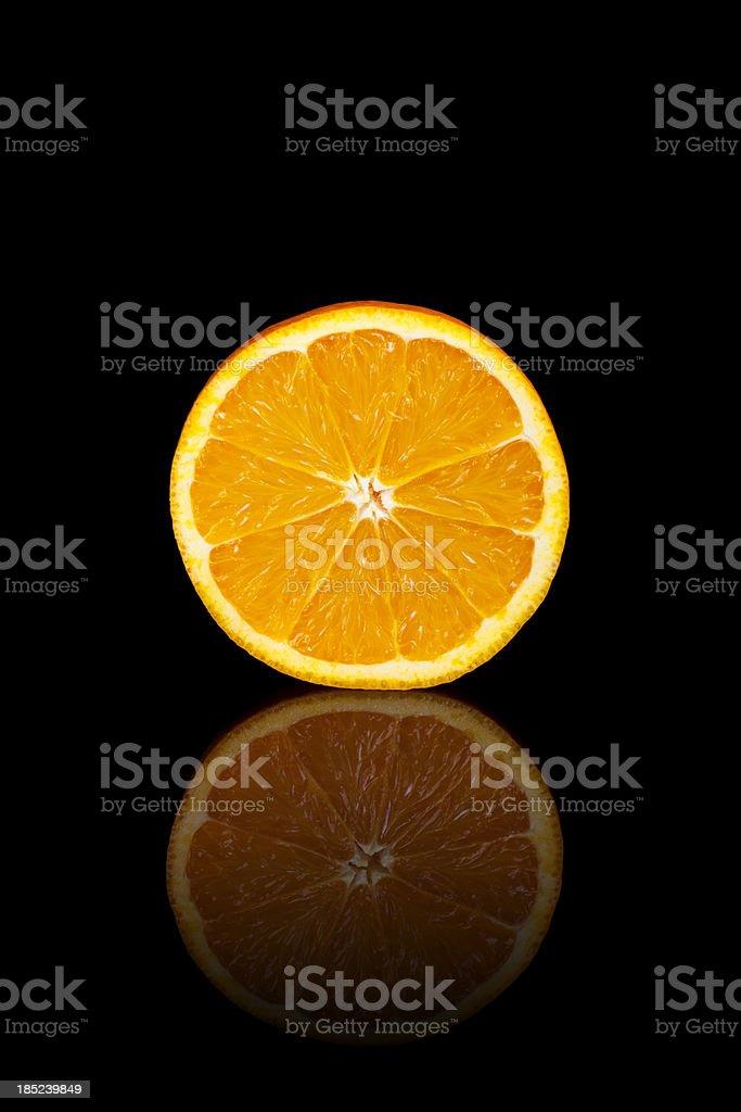 Half orange on a black reflective background royalty-free stock photo