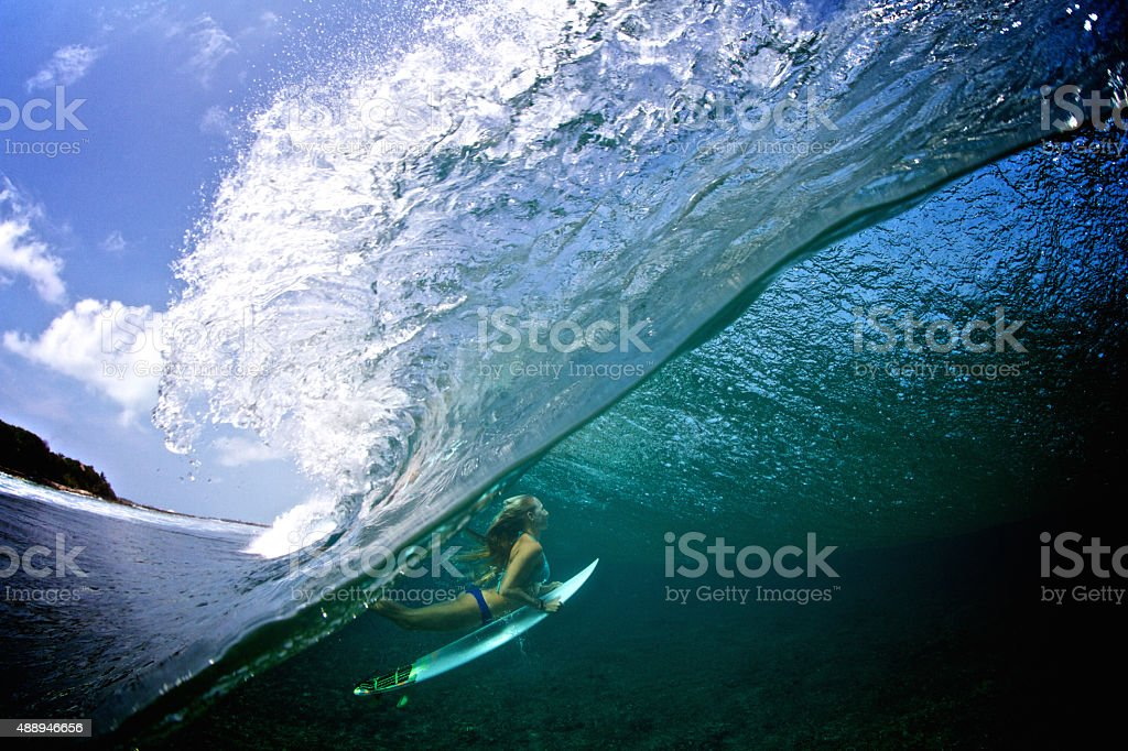 Half over half under girl duck diving a breaking wave stock photo