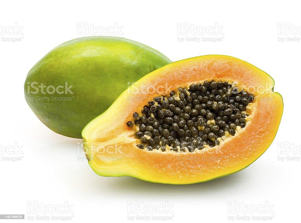 Half papaya showing orange flesh and dark seeds green skin stock photo