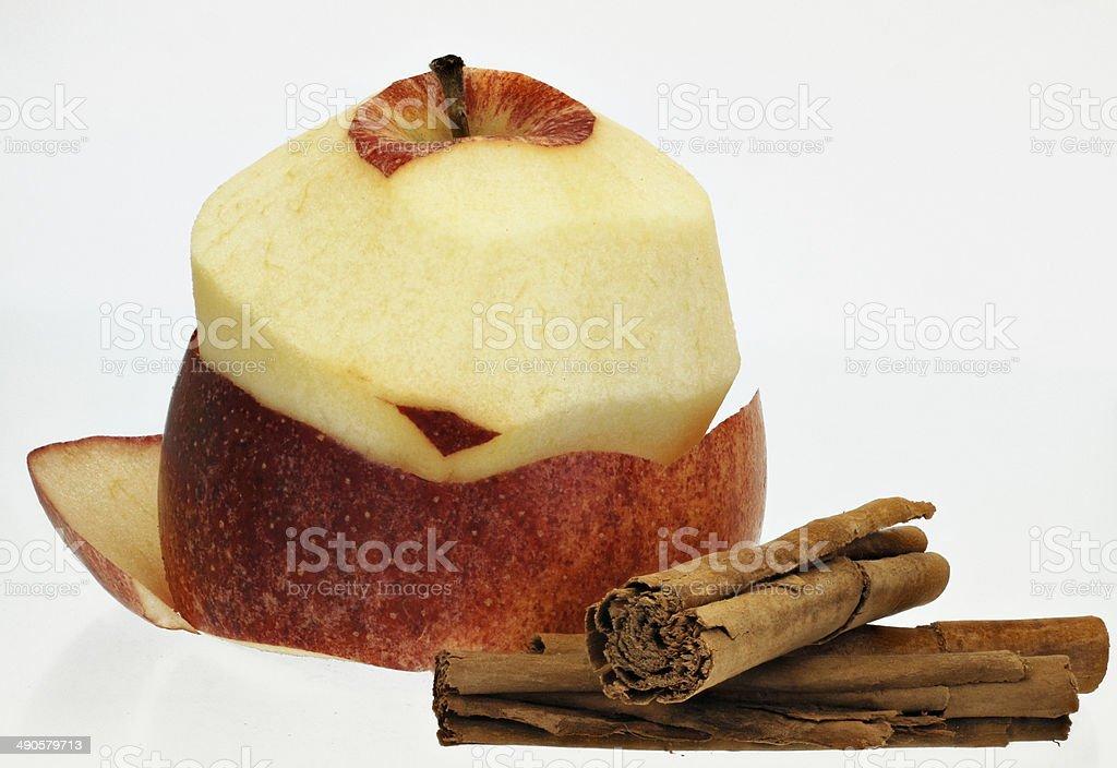 Half peeled apple with cinnamon sticks stock photo