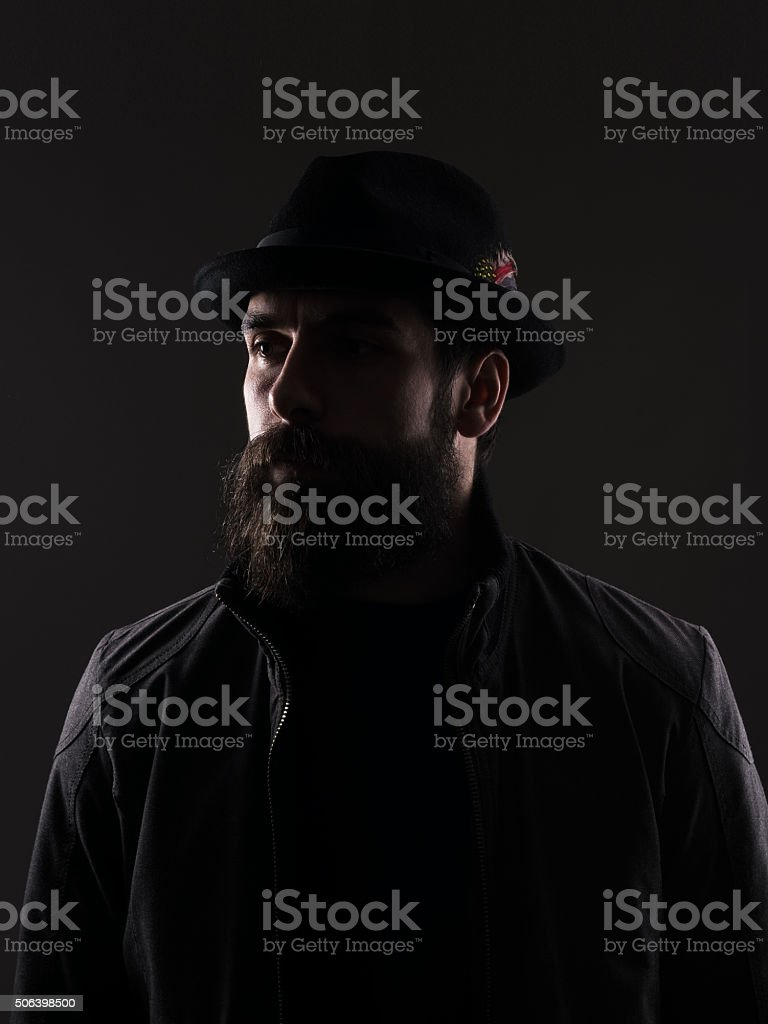 Half profile of bearded man in black hat looking away. stock photo