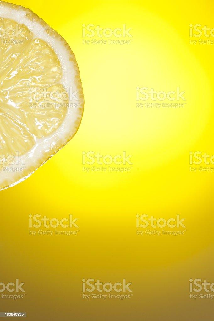 Half Slice Dripping Fresh Sour Lemon on Yellow Background royalty-free stock photo
