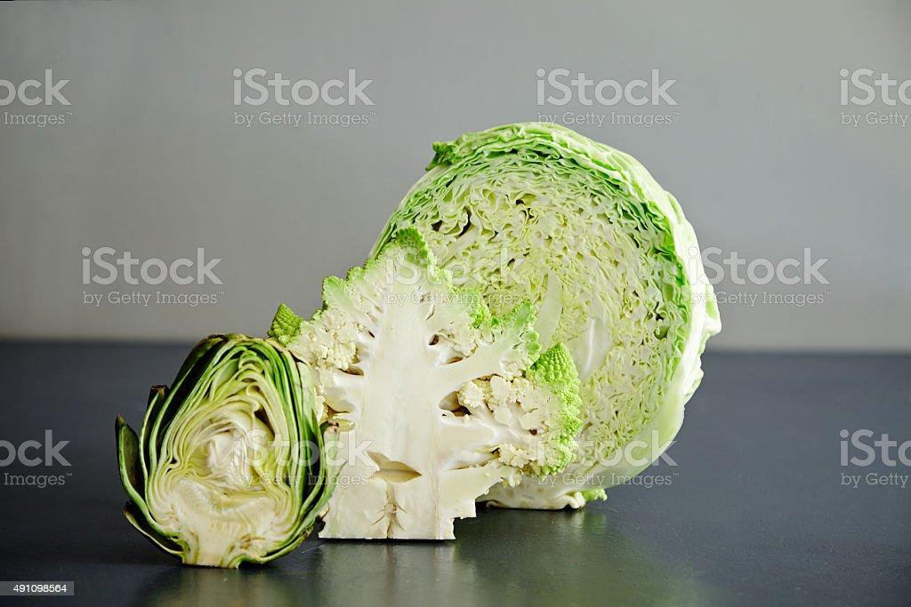 Half splitted artichocke with cabbage and romanesco broccoli stock photo