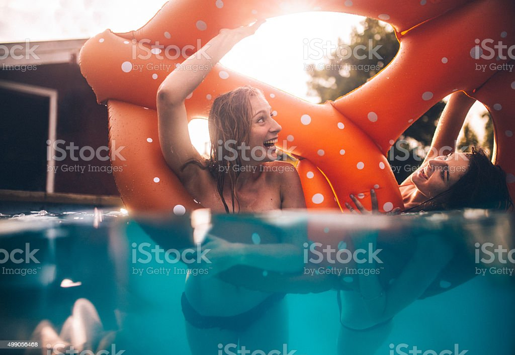 Half submerged image of girls in a pool laughing playfully stock photo