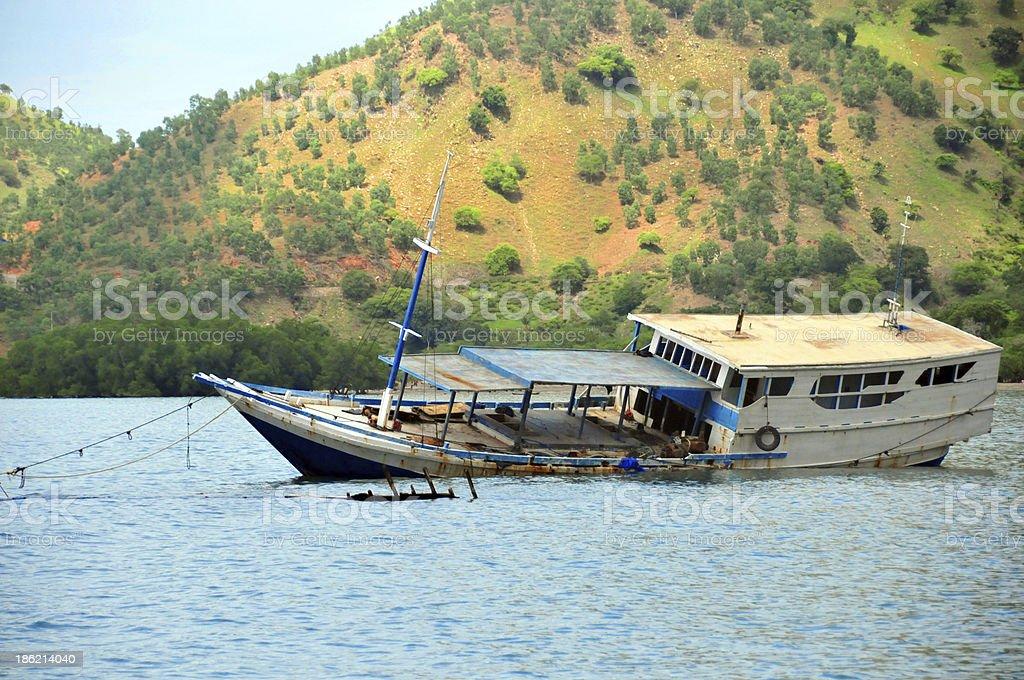 half sunk motorized Lamba Pinisi boat (Timor, Dili) stock photo