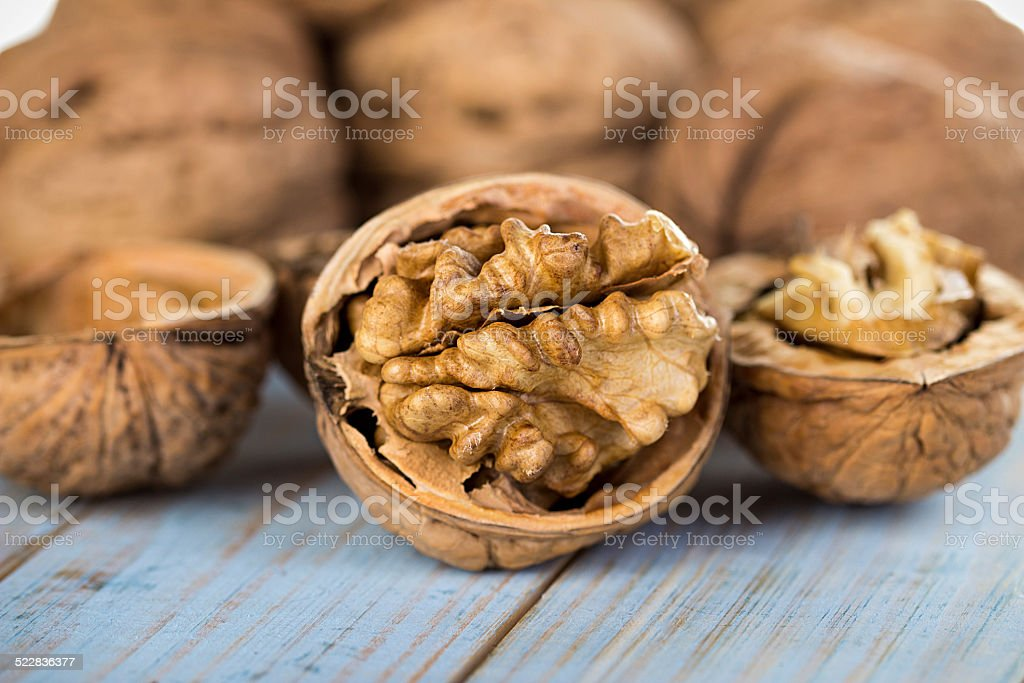 Half walnut kernel and whole walnuts stock photo