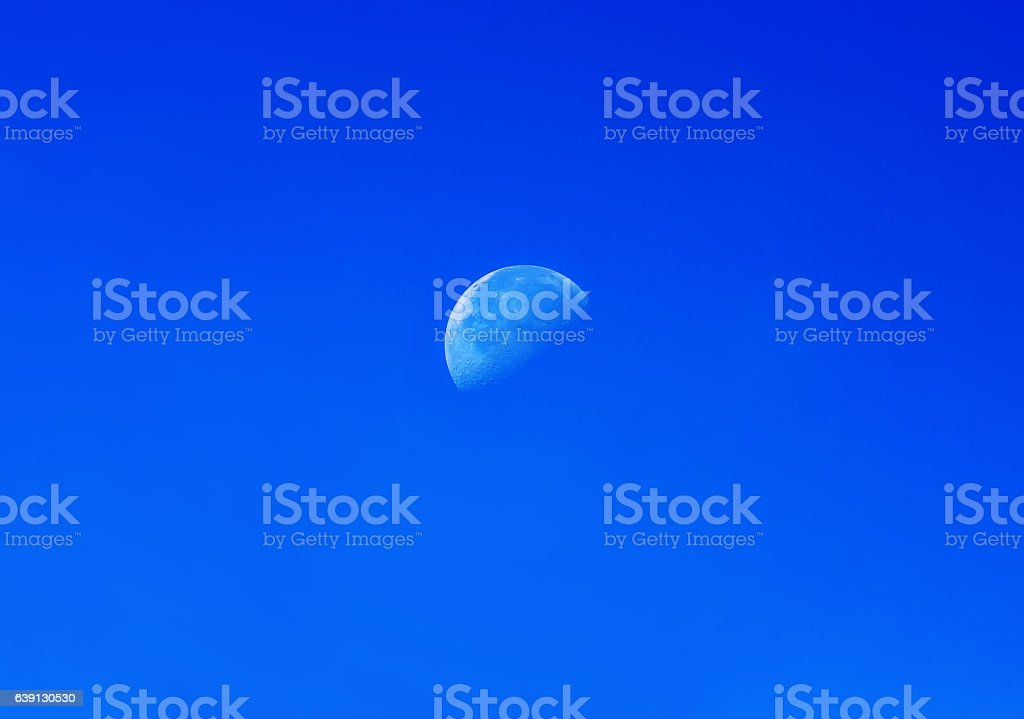 half white moon on blue sky day stock photo
