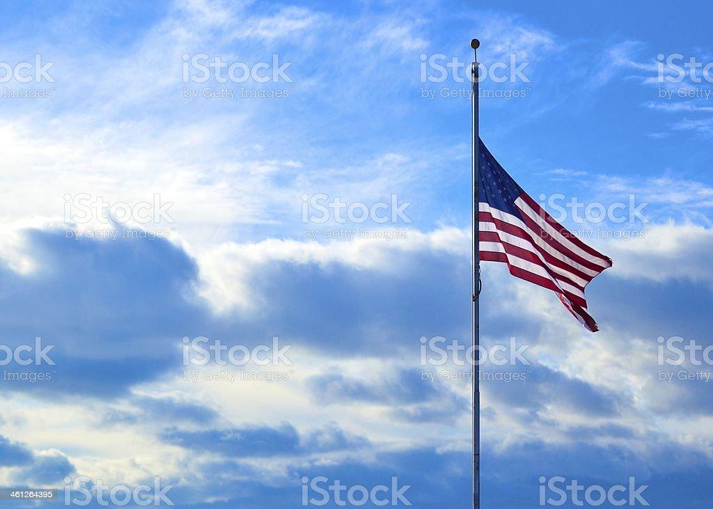 Half-Mast American Flag Against Blue Sky stock photo