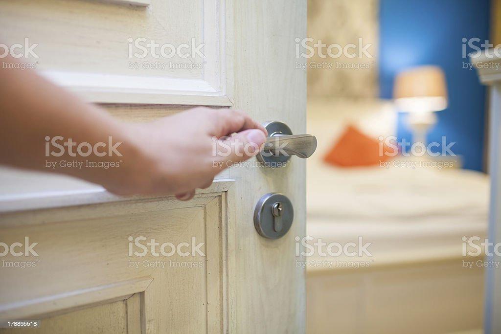half-open door of a bedroom with hand stock photo