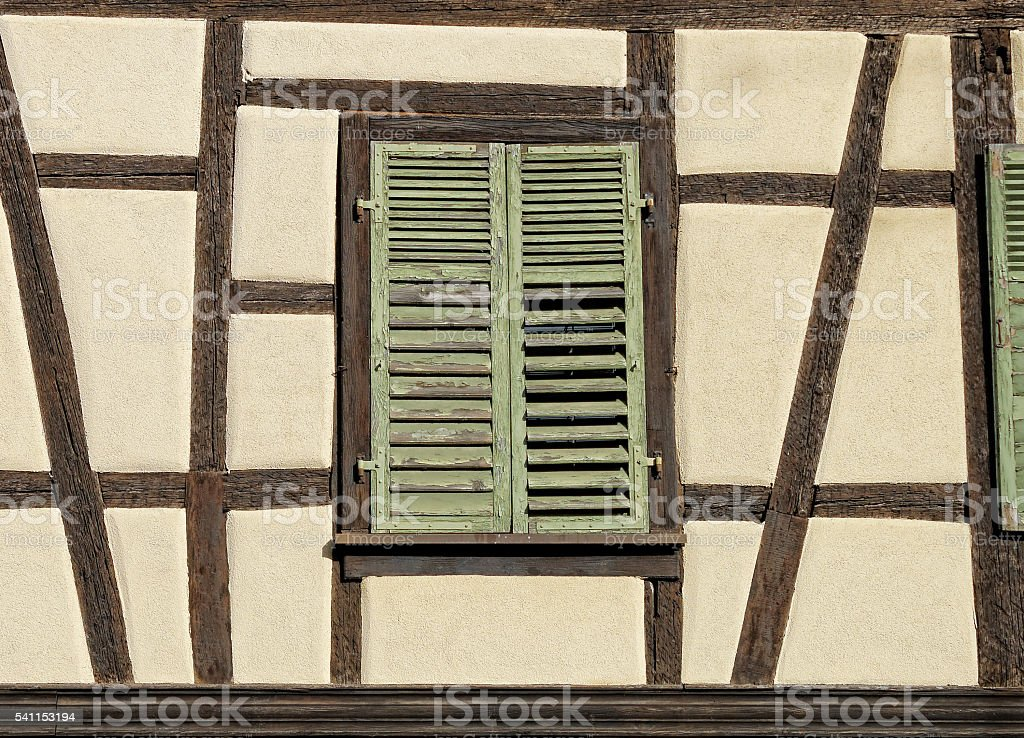 Half-timbered house with green wooden shutter in Ribeauville, Alsace stock photo