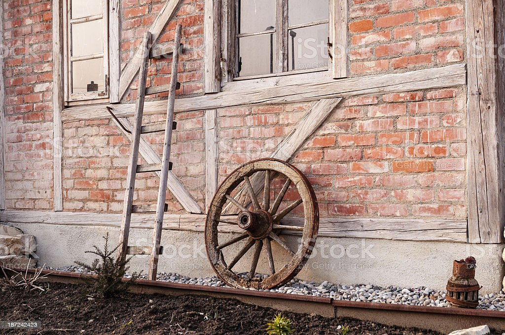 Half-timbered with wooden ladder and old wagon wheel stock photo