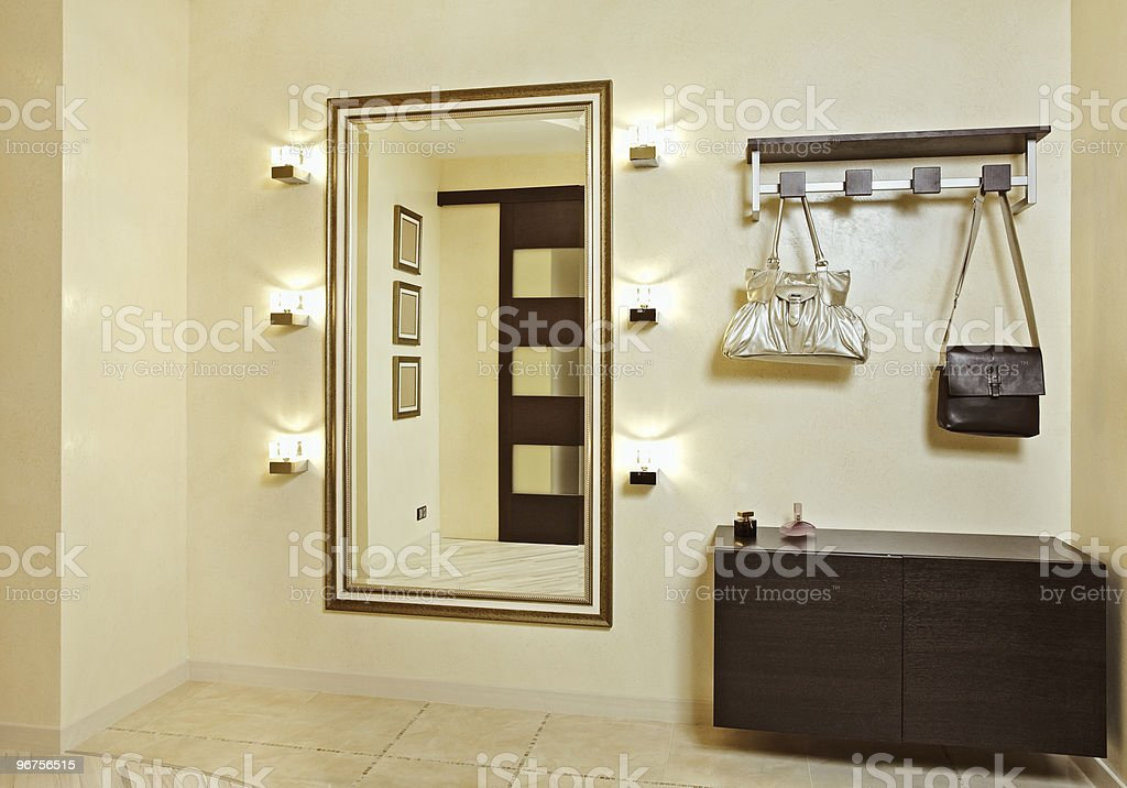 Hall in beige tones with hall-stand and golden mirror stock photo