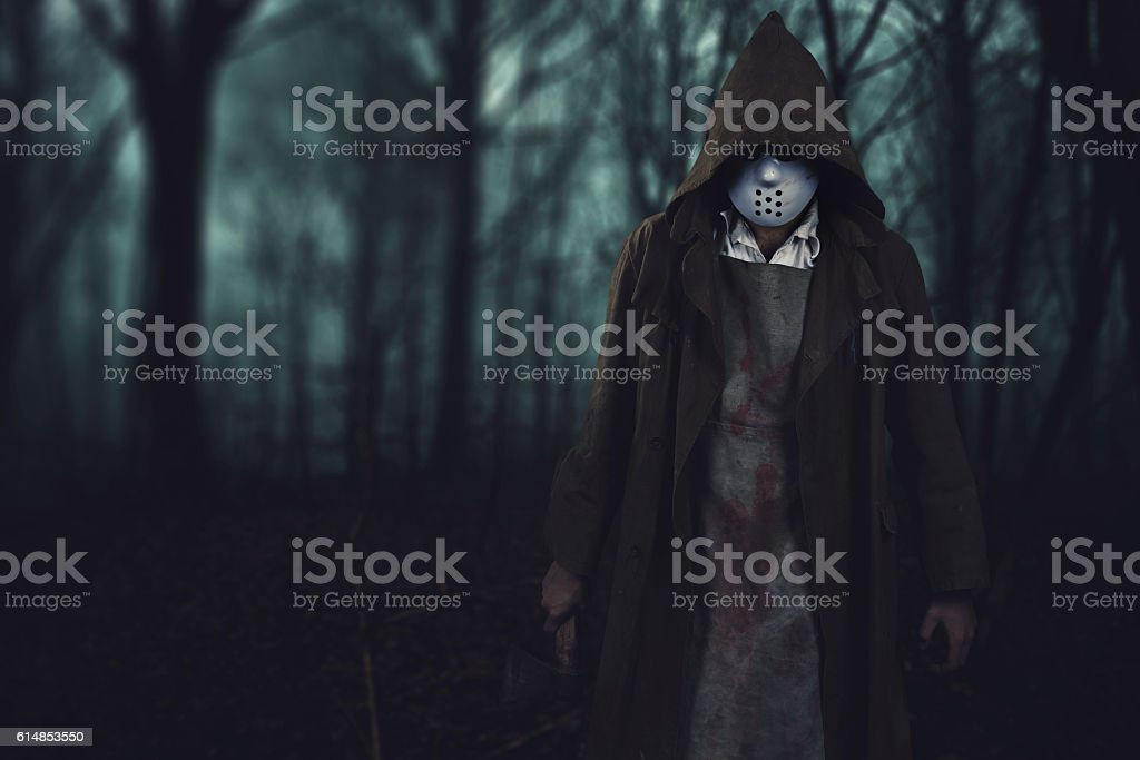 halloween background - bloody serial killer in the scary woods stock photo