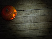 Halloween background of burning pumpkin on a wooden deck.
