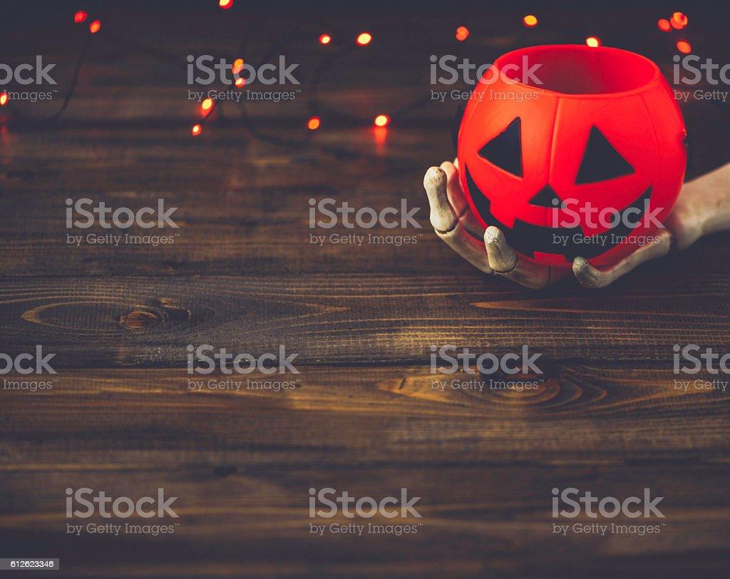 Halloween backgrounds. Skeletal hand holding pumpkin bucket stock photo