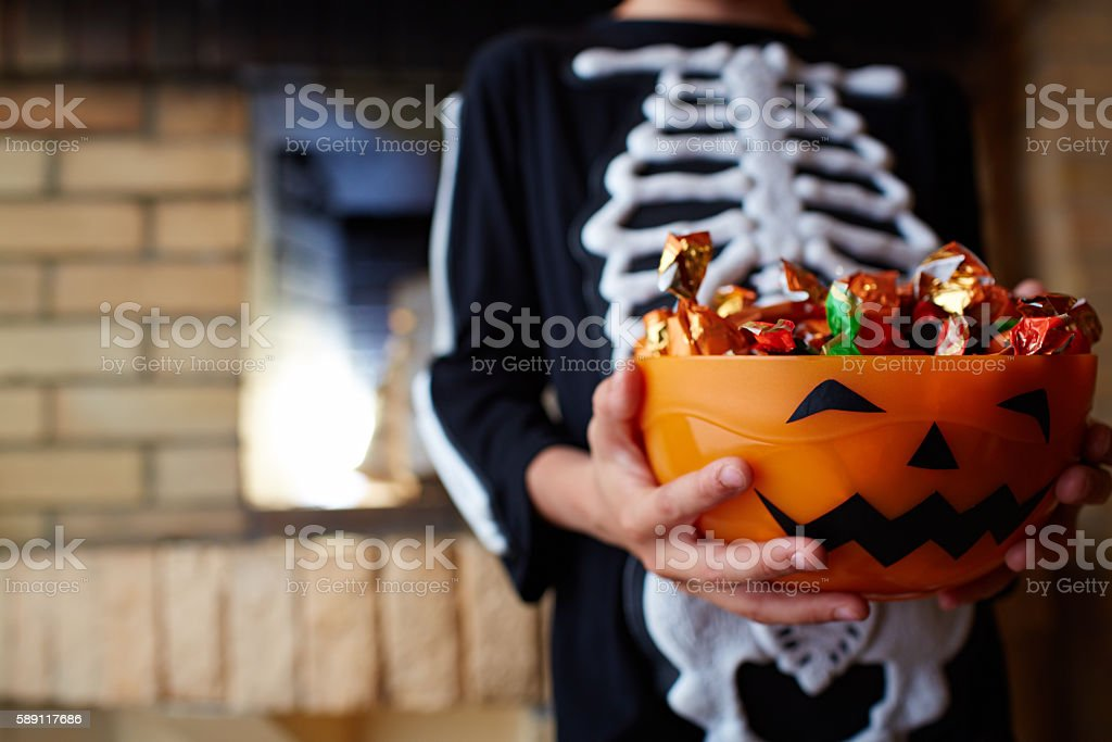 Halloween bowl with chocolate candies given by people stock photo