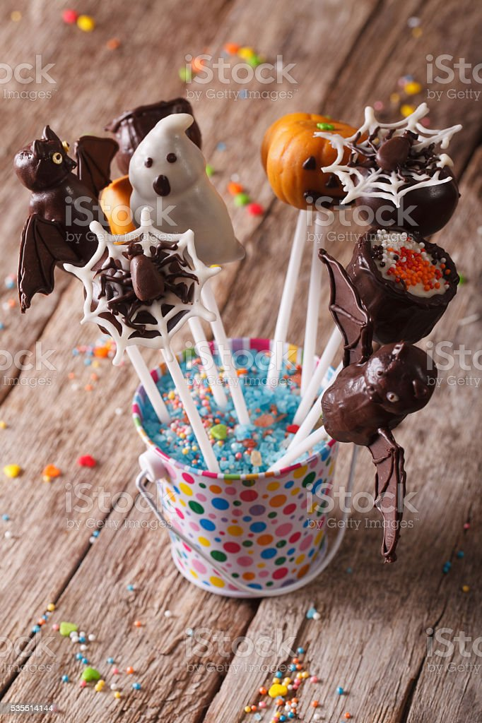 Halloween cake pop decorated with icing on the table. vertical stock photo