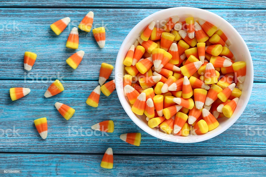 Halloween candy corns in bowl on blue wooden background stock photo