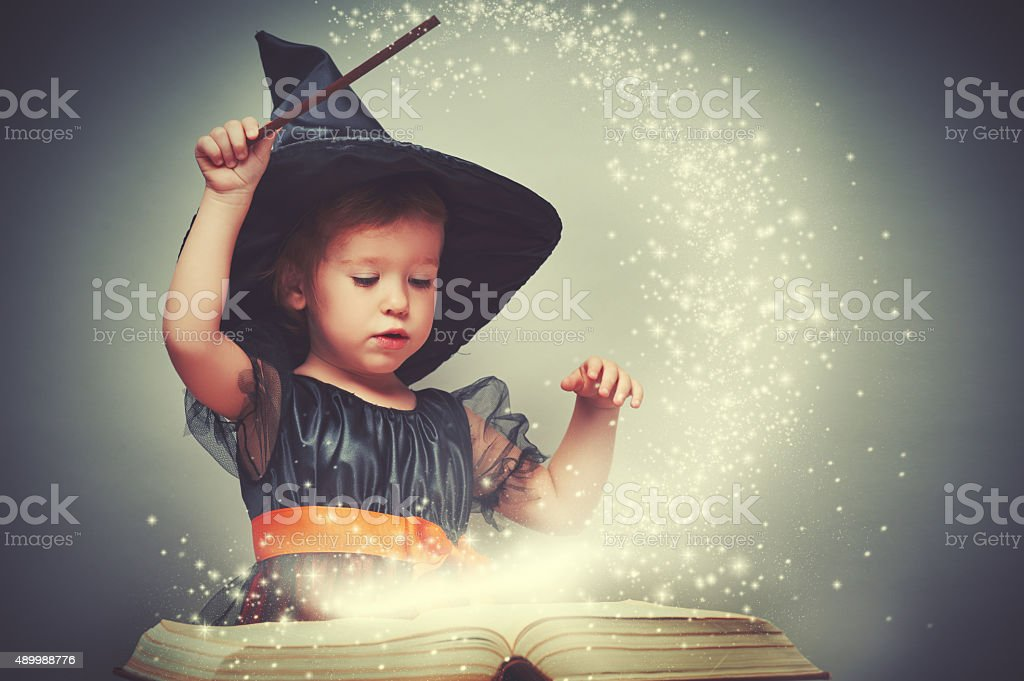 Halloween. cheerful little witch with a magic wand stock photo