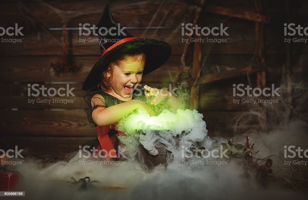 Halloween. child girl witch preparing  potion in cauldron stock photo