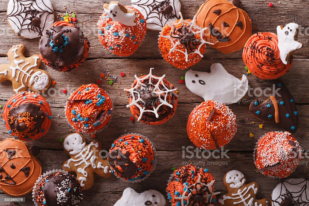 Halloween cupcakes and gingerbread cookies. horizontal top view stock photo