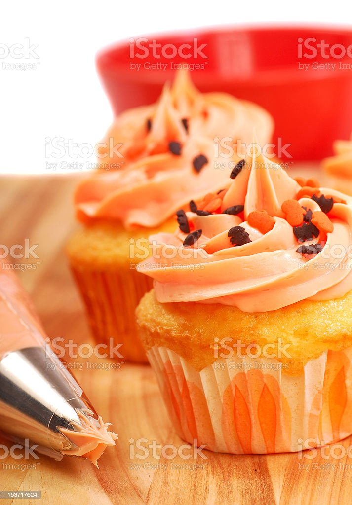 Halloween cupcakes being frosted stock photo