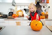 Halloween dressed girl creating pumpkin Jack-O-Lantern