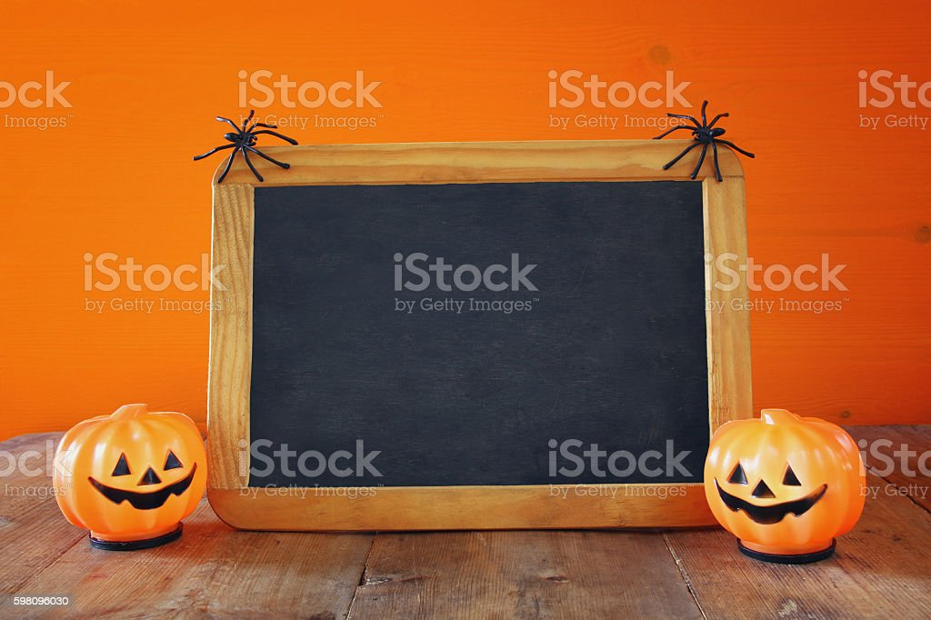 Halloween holiday concept. Cute pumpkins next to empty blackboar stock photo
