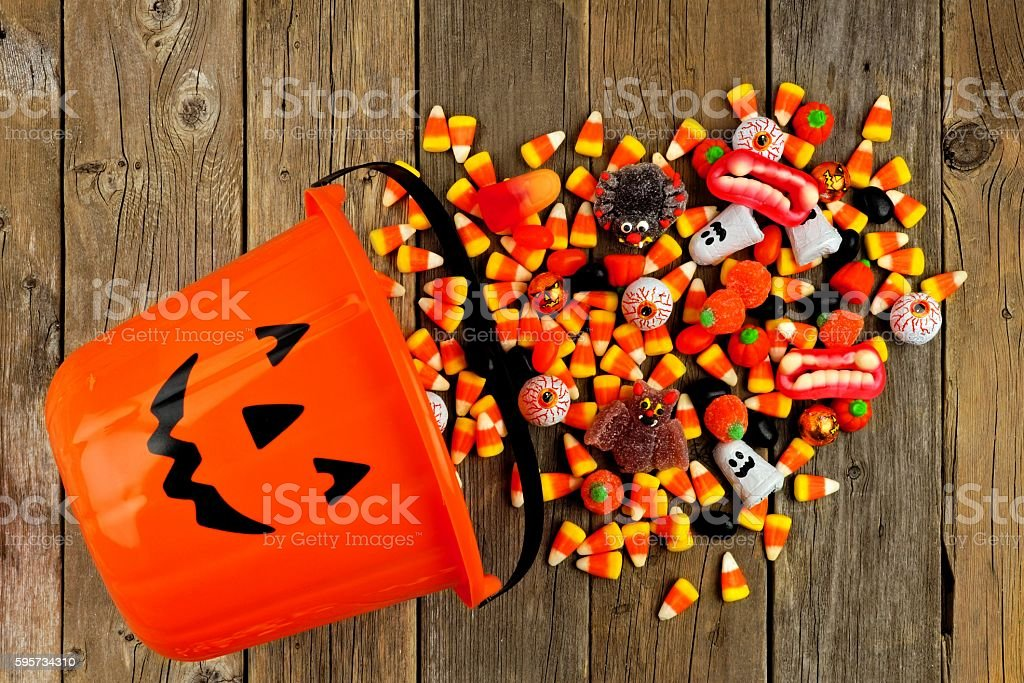 Halloween Jack o Lantern pail with spilling candy over wood stock photo