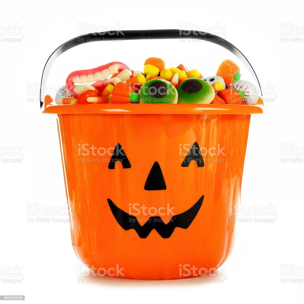 Halloween Jack-o-Lantern candy collector filled with candy over white stock photo