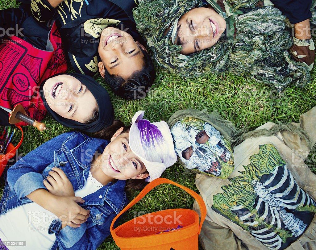 halloween kids laying on grass stock photo
