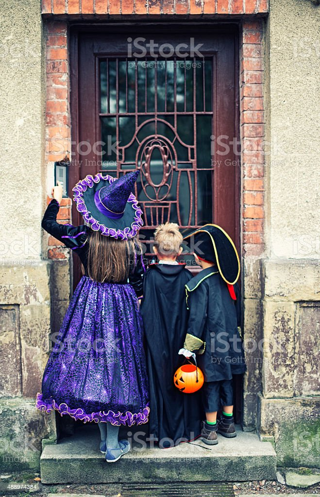 Halloween kids ringing the doorbell of an old scary house stock photo