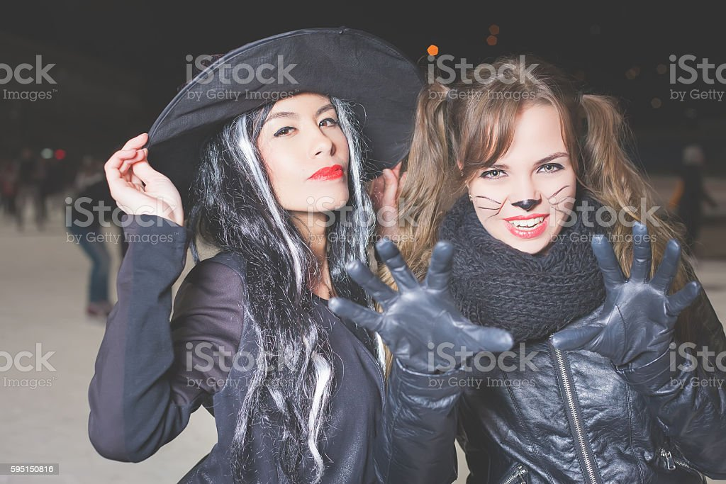 Halloween party! Young women like witch and cat role stock photo