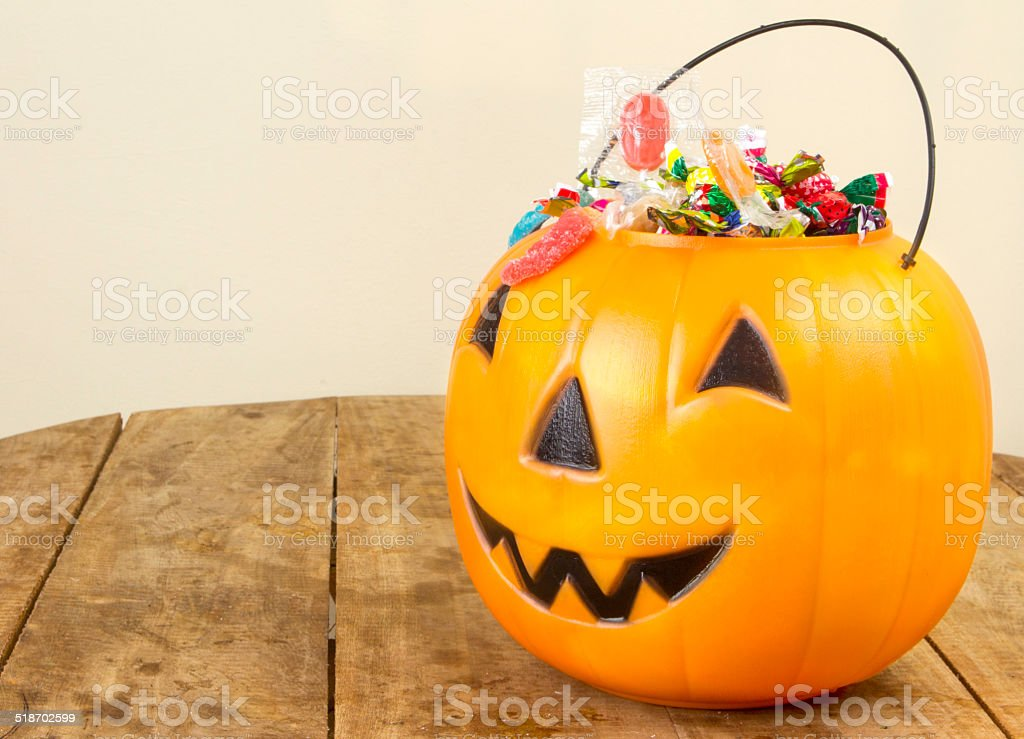 Halloween plastic pumpkin filled with candy on wooden table stock photo