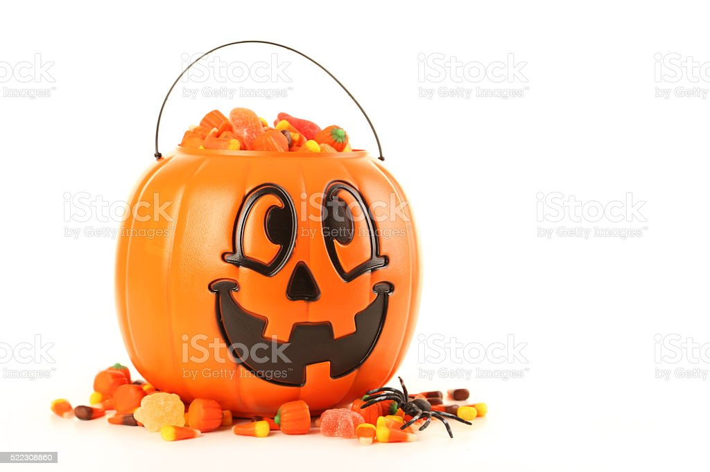 Halloween pumpkin basket full of candies isolated on a white stock photo