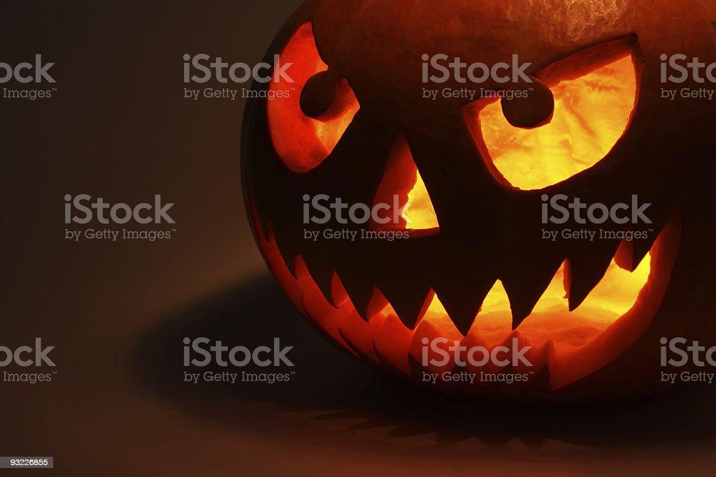 A Halloween pumpkin glowing in the dark royalty-free stock photo