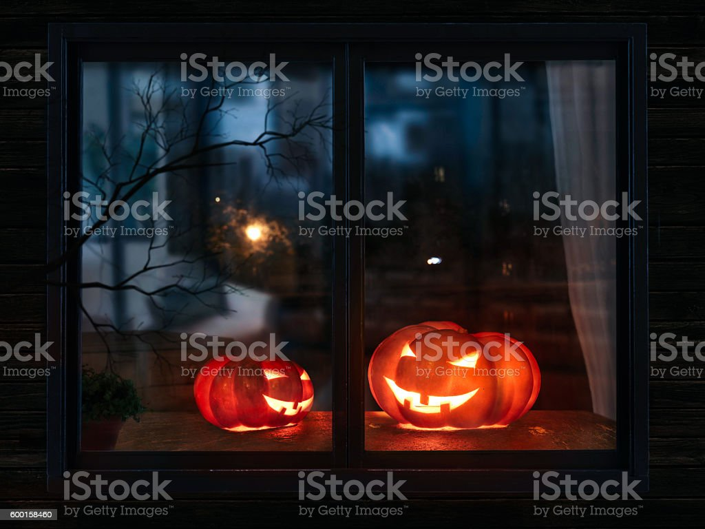 Halloween pumpkin in the mystical house window at night stock photo