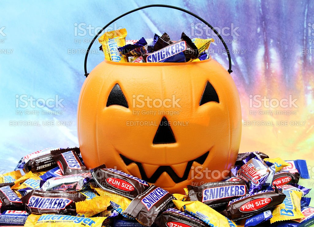 Halloween pumpkin with trick or treat candy. stock photo