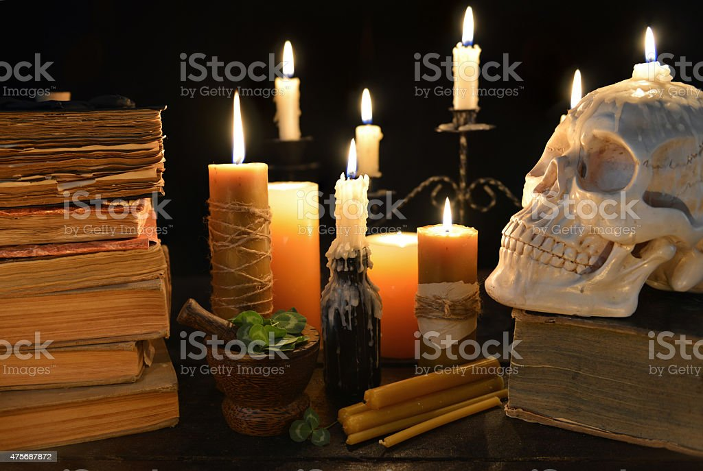 Halloween still life with candles, skull and books stock photo