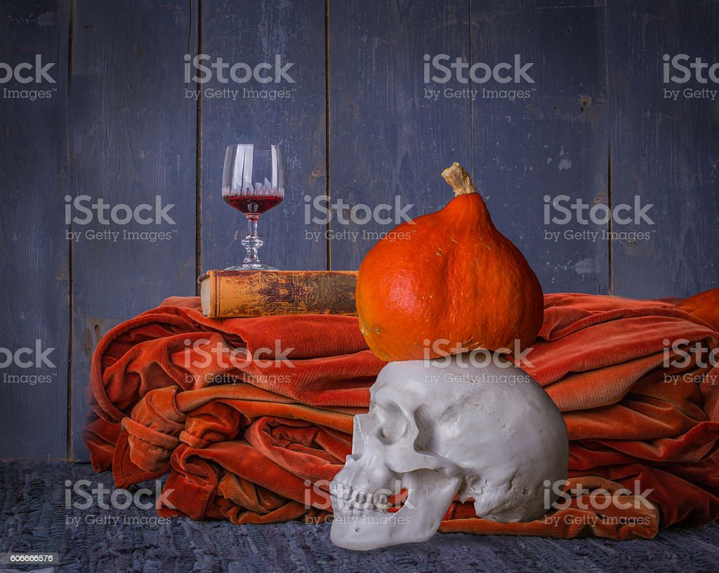Halloween still life with skull, book, pumpkin and red wine stock photo
