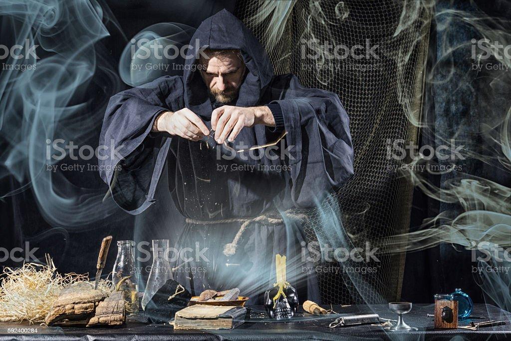 Halloween. The medieval alchemist holds magic ritual smoke stock photo
