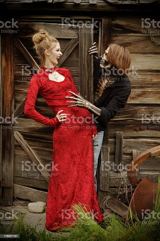 Halloween: vampire lady in red dress and skeleton man stock photo