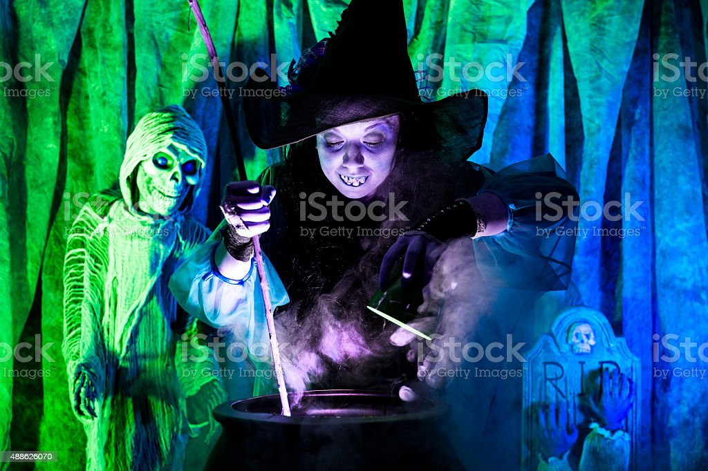 Halloween:  Witch cooking her brew for special guests. Zombie. Cauldron. stock photo