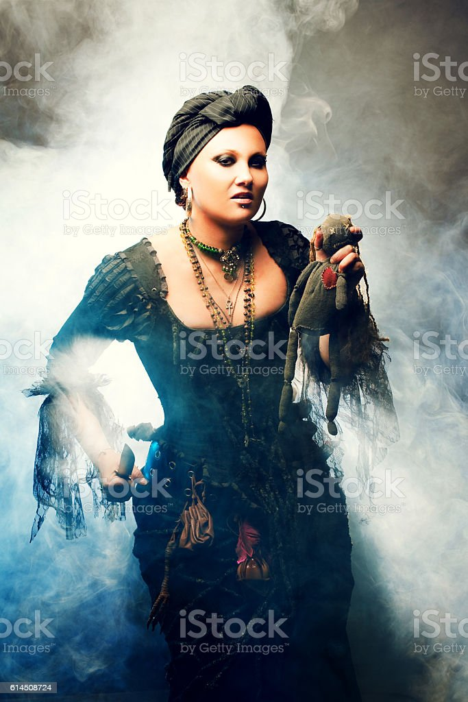 Halloween Witch creates magic. Attractive woman in witches costume with stock photo