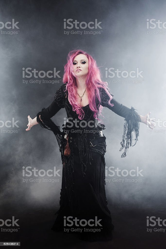 Halloween Witch creates magic. Attractive woman with red hair in stock photo