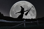 Halloween witch silhouette flying with broomstick. Full Moon.