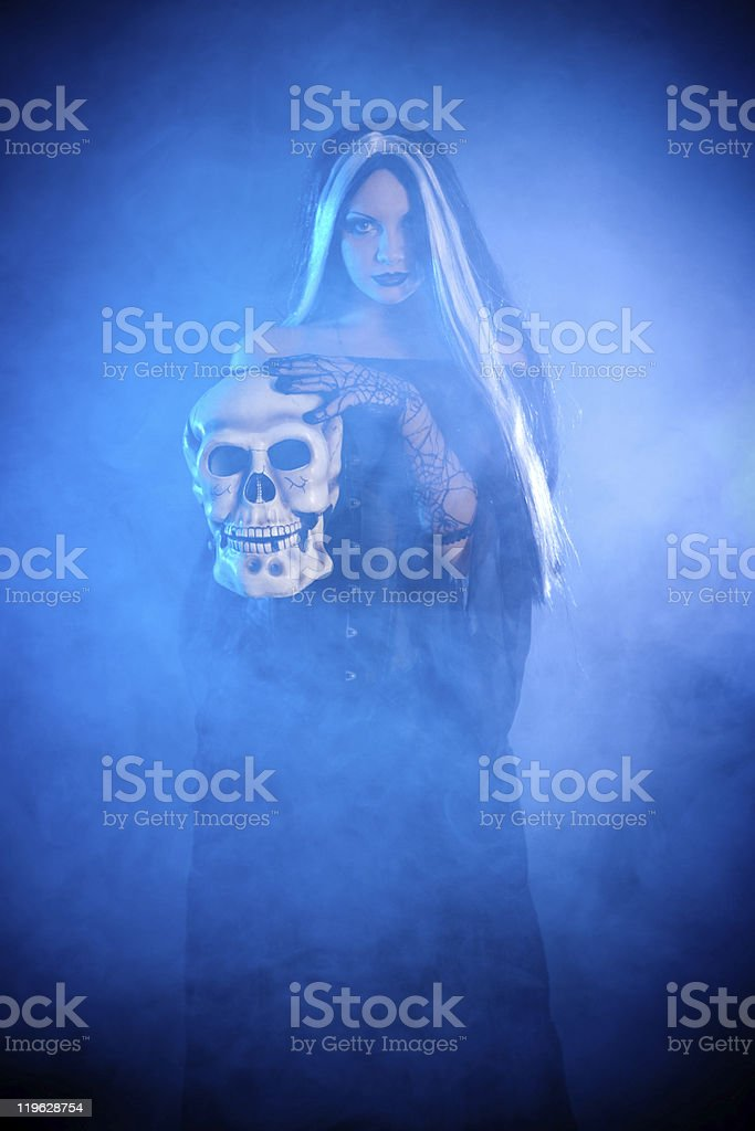 Halloween witch with a skull stock photo